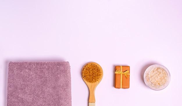 Asciugamano da bagno in spugna, spazzola per massaggi a secco, sapone, sale da bagno marino su sfondo bianco. disposizione piatta, copia spazio, posto per il testo. il concetto di cura del corpo, igiene personale. vista dall'alto