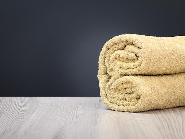 Asciugamano in spugna come composizione spa sulle tavole di legno e sullo sfondo grigio.