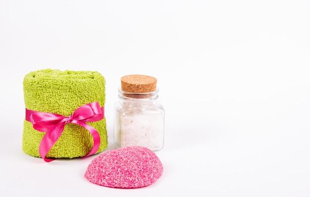Asciugamano di spugna, sapone rosa e sale marino su fondo bianco.