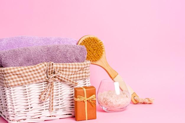 Asciugamani di spugna in un cesto, sapone naturale, sale marino e una spazzola da massaggio su uno sfondo rosa. concetto di cura del corpo. copia spazio, posto per il testo. avvicinamento