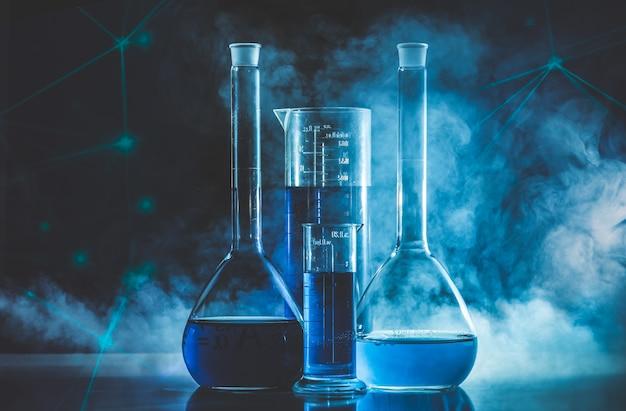 Provetta e pallone con liquido blu e fumo blu. chimica e concetto di laboratorio.