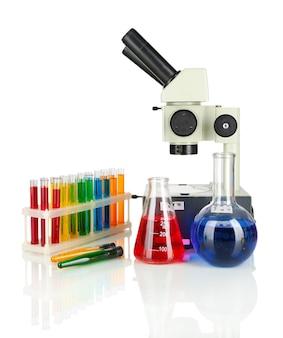 Provette con liquidi colorati e microscopio isolato su bianco