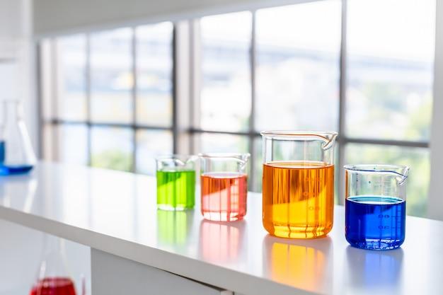 Provette con la vetreria per laboratorio sulla tavola in laboratorio, ricerca e concetto scientifico