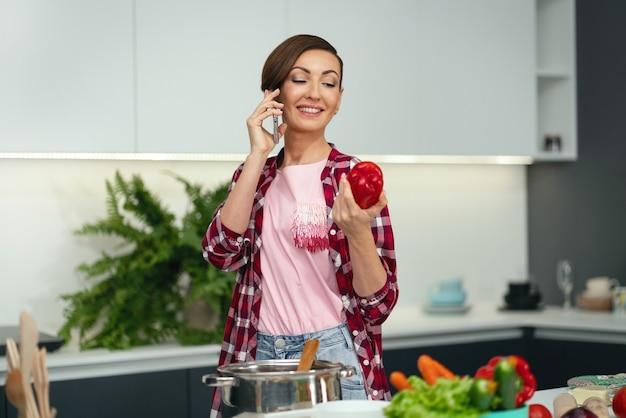 Testare il cibo mentre parla al telefono casalinga con un taglio di capelli corto. cucinare il pranzo per la famiglia nella cucina moderna. cibo sano a casa.