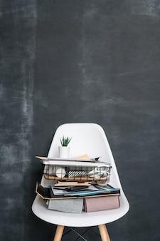 Campioni di tessuto, cesto con forniture per il lavoro di designer contemporaneo di interni e altre cose sulla sedia di plastica contro la lavagna