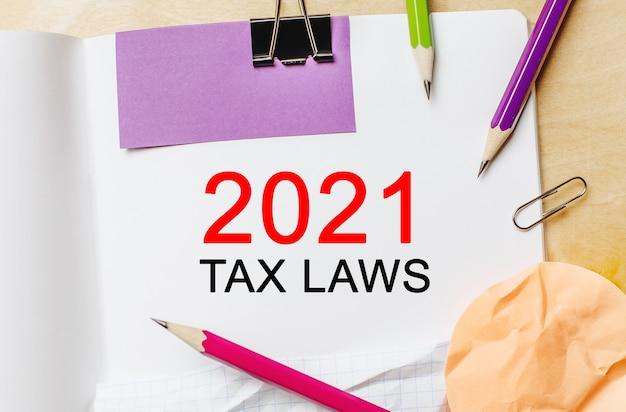 Testo leggi fiscali 2021 su uno sfondo bianco con matite, adesivi e graffette. concetto di affari