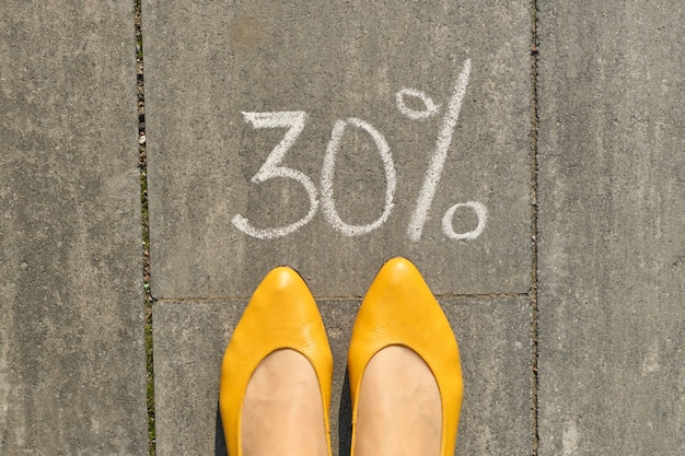Mandi un sms al 30 per cento scritto su pavimentazione grigia con gambe di donna