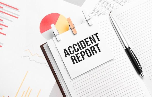 Rapporto di incidente del testo sugli adesivi sul diario con gli strumenti dell'ufficio