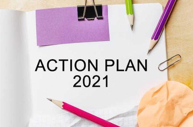 Testo piano d'azione 2021 su sfondo bianco con matite, adesivi e graffette. concetto di affari