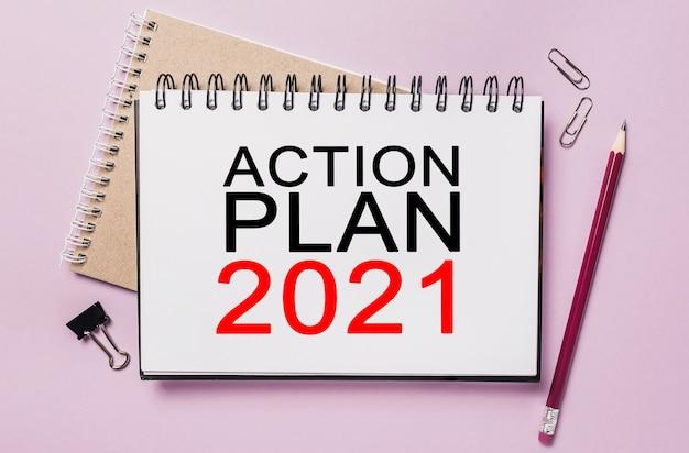 Testo piano d'azione 2021 su un blocco note bianco con sfondo di cancelleria per ufficio. lay piatto sul concetto di affari, finanza e sviluppo