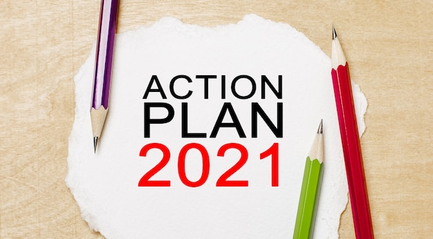 Testo piano d'azione 2021 su un blocco note bianco con matite su fondo in legno. concetto di affari