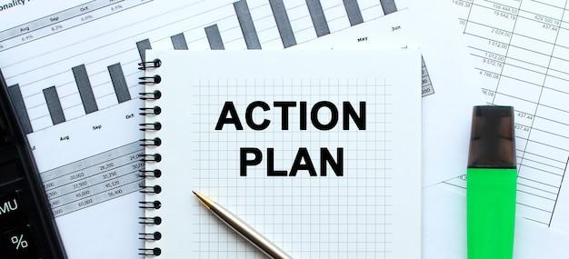 Piano d'azione del testo sulla pagina di un blocco note che si trova sui grafici finanziari sulla scrivania dell'ufficio