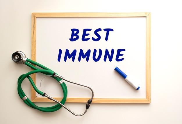 Il testo best immune è scritto su una lavagna bianca con un pennarello. nelle vicinanze c'è uno stetoscopio. concetto medico.