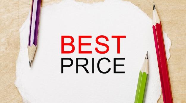 Testo miglior prezzo su un blocco note bianco con matite su uno sfondo di legno. concetto di affari