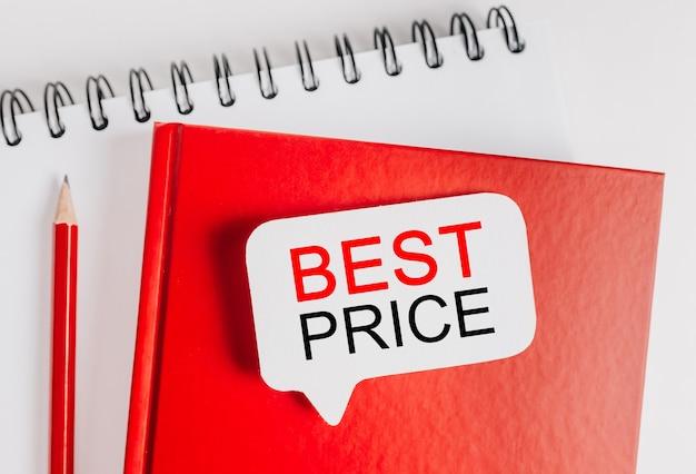 Testo miglior prezzo su un adesivo bianco su un blocco note rosso con sfondo di cancelleria per ufficio. piatto disteso sul concetto di business, finanza e sviluppo