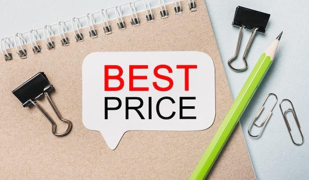 Testo miglior prezzo su un adesivo bianco con sfondo di cancelleria per ufficio. piatto disteso sul concetto di business, finanza e sviluppo