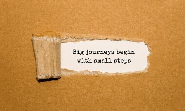 Il testo i grandi viaggi iniziano con piccoli passi che appaiono dietro la carta marrone strappata