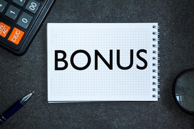 Testo bonus. scrivania da ufficio, calcolatrice, blocco note con documenti. concetto di affari