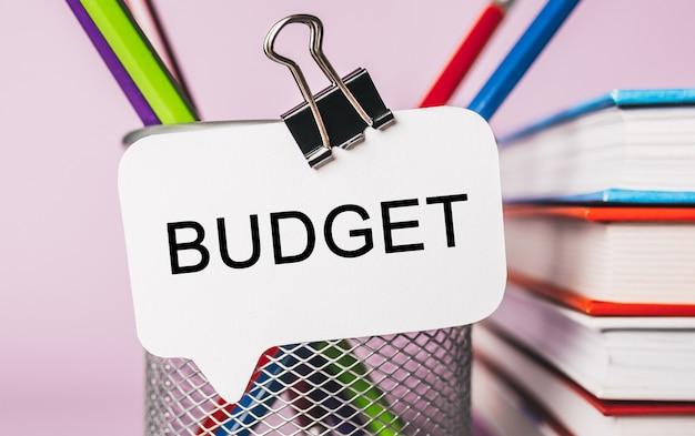 Budget di testo su un adesivo bianco con sfondo di cancelleria per ufficio. piatto disteso sul concetto di business, finanza e sviluppo