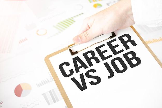 Testo carriera vs lavoro sul piatto di carta bianca nelle mani dell'uomo d'affari con diagramma finanziario. concetto di affari
