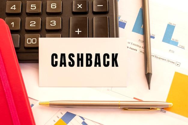 Testo cashback su carta bianca. penna in metallo, calcolatrice e grafici finanziari. concetto finanziario.
