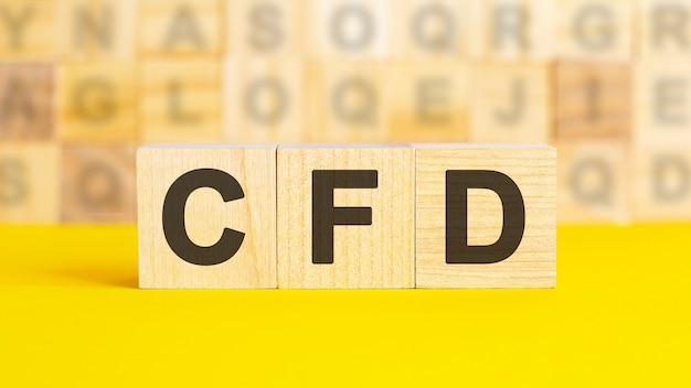 Il testo cfd è scritto su cubi di legno su una superficie gialla brillante. sullo sfondo ci sono file di cubi con lettere diverse. concetto di affari. cfd - abbreviazione di contratti per differenza