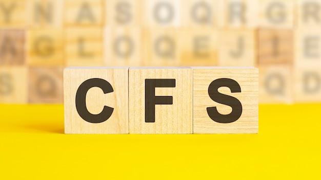 Il testo cfs è scritto su cubi di legno su una superficie giallo brillante. sullo sfondo ci sono file di cubi con lettere diverse. concetto di affari. cfs - abbreviazione di bilancio consolidato