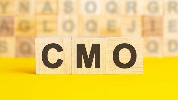 Il testo cmo è scritto su cubi di legno su una superficie giallo brillante. sullo sfondo ci sono file di cubi con lettere diverse. concetto di affari. cmo - abbreviazione di chief marketing officer