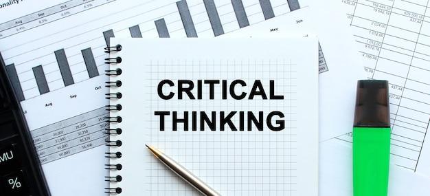 Testo pensiero critico sulla pagina di un blocco note che si trova sui grafici finanziari sulla scrivania dell'ufficio. vicino alla calcolatrice e al pennarello.