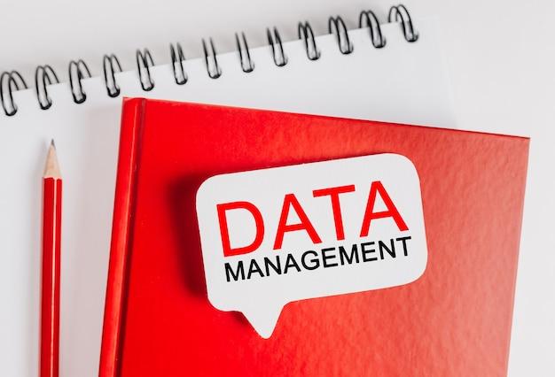 Testo gestione dei dati su un adesivo bianco su un blocco note rosso con sfondo di cancelleria per ufficio. piatto disteso sul concetto di business, finanza e sviluppo