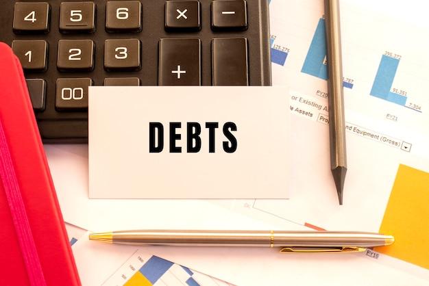 Debiti di testo su carta bianca. penna in metallo, calcolatrice e grafici finanziari. concetto finanziario.