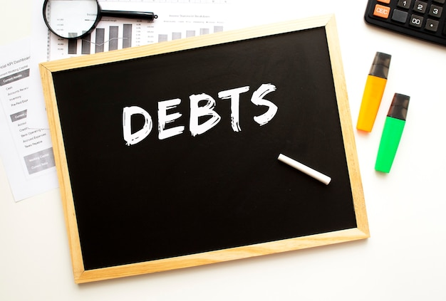 Testo debiti scritti in gesso su una tavola di ardesia scrivania da ufficio con forniture per ufficio