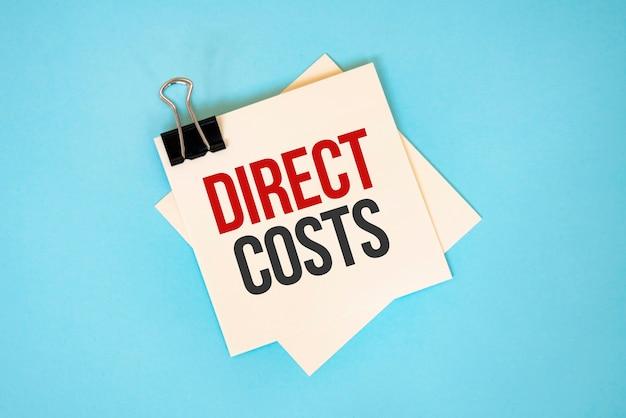 Testo costi diretti su foglietti adesivi con copia spazio e graffetta