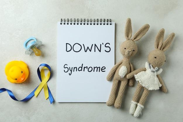 Testo di sindrome di down, giocattoli, ciuccio e nastri di consapevolezza su bianco strutturato