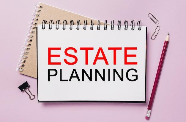 Testo pianificazione immobiliare su un blocco note bianco con spazio cancelleria per ufficio