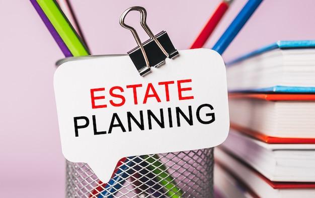 Testo pianificazione immobiliare su un adesivo bianco con cancelleria per ufficio