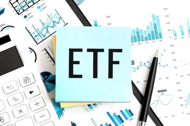 Testo etf exchange traded fund su adesivo blu, calcolatrice, penna, grafici. disposizione piana di affari.
