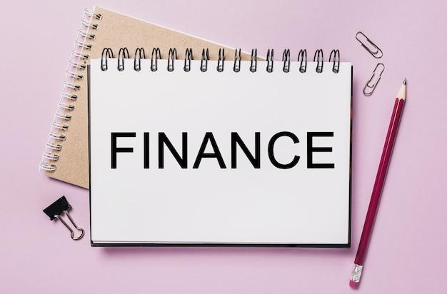 Testo finanza su un blocco note bianco con cancelleria per ufficio