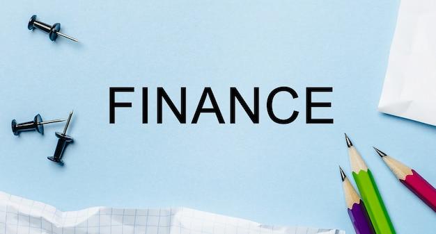 Testo finanza su un blocco note bianco con matite su sfondo blu. concetto di affari