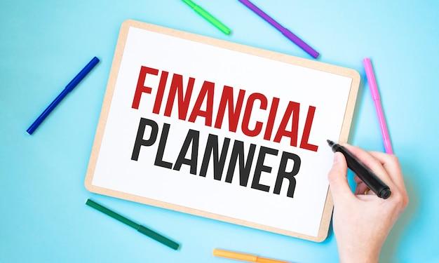 Testo pianificatore finanziario su un notebook circondato da pennarelli colorati, idea di concetto di business,