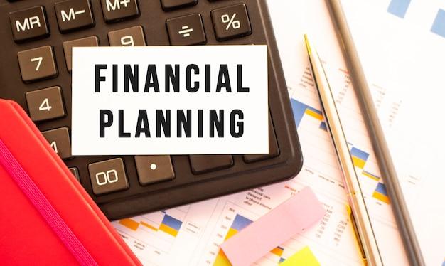 Testo pianificazione finanziaria su carta bianca con penna in metallo, calcolatrice e grafici finanziari.