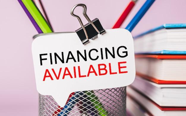 Finanziamento del testo disponibile su un adesivo bianco con cancelleria per ufficio