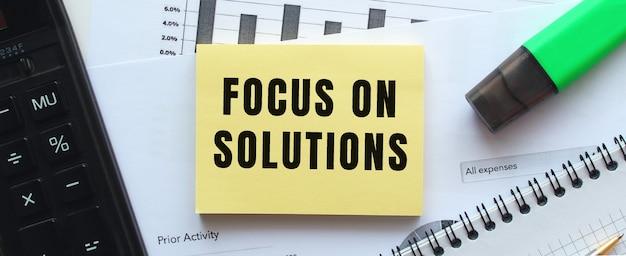Testo focus on solutions sulla pagina di un blocco note che giace sui grafici finanziari sulla scrivania dell'ufficio. vicino alla calcolatrice. concetto di affari.