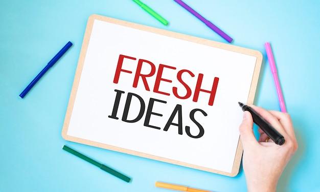 Testo nuove idee su un taccuino circondato da pennarelli colorati, idea di concetto di affari,