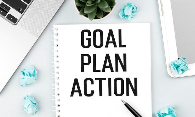 Testo azione piano obiettivo sulla nota. computer portatile, pezzi di carta, penna e pianta sulla scrivania dell'ufficio. disposizione piana, vista dall'alto. concetto di pianificazione.