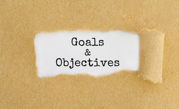 Obiettivi e obiettivi del testo che appaiono dietro carta marrone strappata.