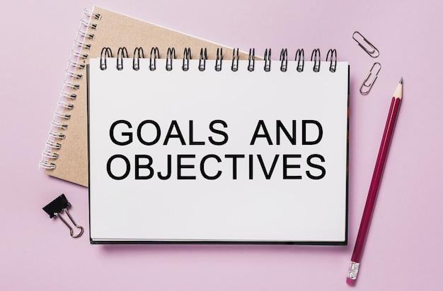 Testo obiettivi e obiettivi su un adesivo bianco con sfondo di cancelleria per ufficio. piatto disteso sul concetto di business, finanza e sviluppo