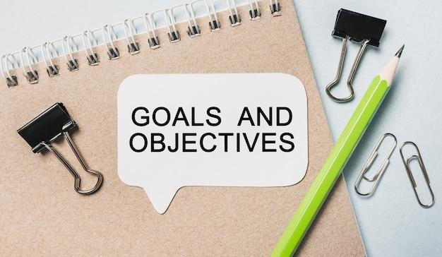 Obiettivi e obiettivi del testo su un adesivo bianco con cancelleria per ufficio
