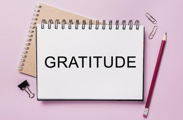 Testo gratitudine su un adesivo bianco con sfondo di cancelleria per ufficio. piatto disteso sul concetto di business, finanza e sviluppo