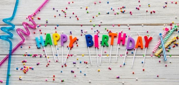 Testo buon compleanno da lettere di candela con accessori di compleanno, candele e coriandoli su fondo di legno bianco